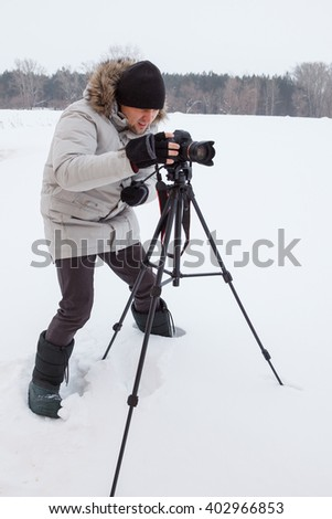 Young man taking photo with professional digital camera - stock photo