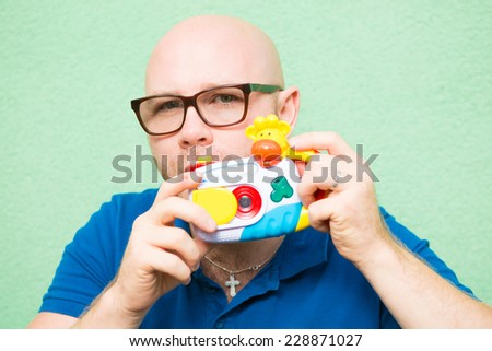 Young man taking photo with toy camera, focus on face - stock photo