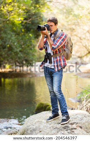 young man taking photos in mountain valley with dslr camera - stock photo