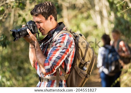 young man taking photos with dslr camera during hiking with friends - stock photo
