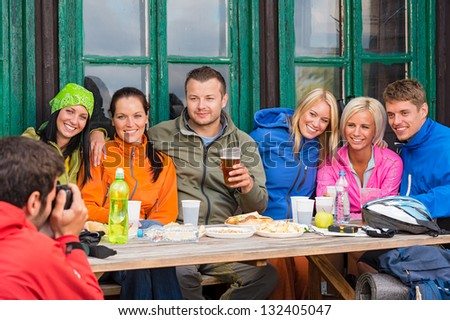 Young man taking picture of smiling friends during weekend - stock photo