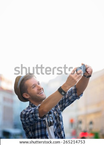 Young man taking pictures on your phone - stock photo