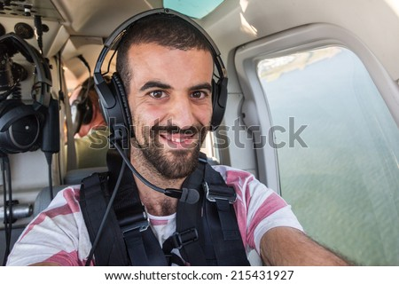 Young Man Taking Selfie in Helicopter Cabin While Flying - stock photo