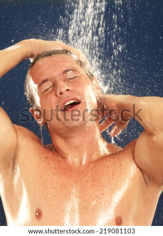 Young man taking shower. - stock photo
