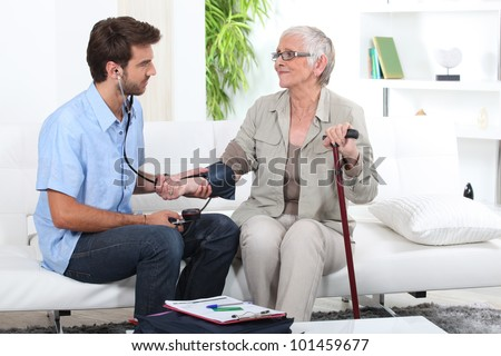 Young man taking the blood pressure of an older lady - stock photo