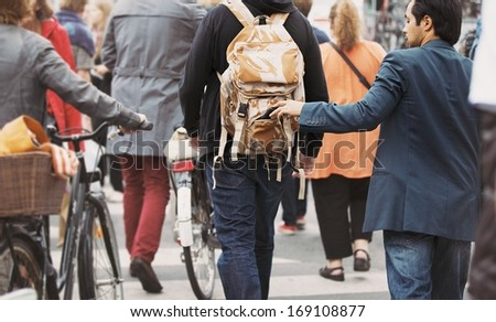 Young man taking wallet from backpack of a man walking on street during daytime. Pickpocketing on the street during daytime - stock photo