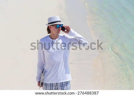 Young man talking by cell phone on tropical beach - stock photo