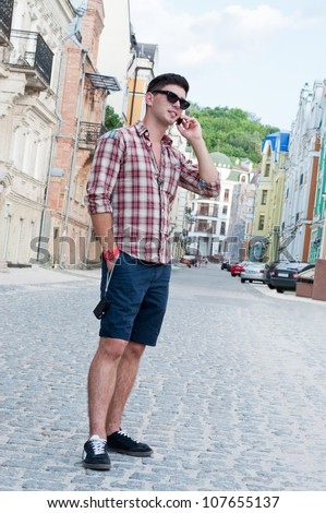 Young man talking on a cell phone on the street. - stock photo