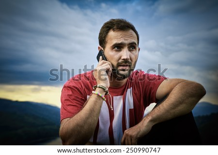 Young man talking on his cell phone. Handsome guy with beard and cell phone in nature. Outdoor picture. - stock photo