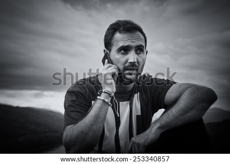 Young man talking on his cell phone. Handsome guy with beard and mobilephone in nature. Outdoor picture. Black & white picture. - stock photo