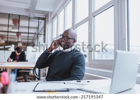 Young man talking on his mobile phone in office. African executive sitting at his desk with laptop - stock photo