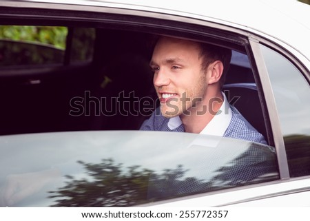Young man talking on phone in limousine on a sunny day - stock photo