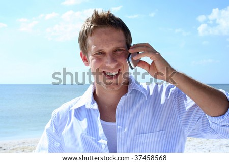 Young man talking on phone on the beach - stock photo