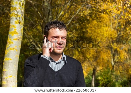 Young man talking on the mobile phone in a park in autumn - stock photo
