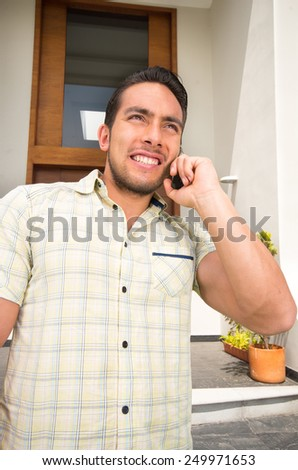 young man talking on the phone outside his house - stock photo