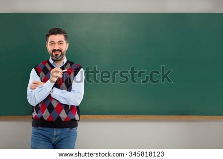 Young man teacher on green board. - stock photo