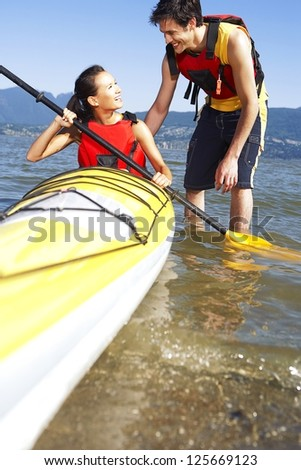 Young man teaches his girlfriend how to paddle in a kayak - stock photo