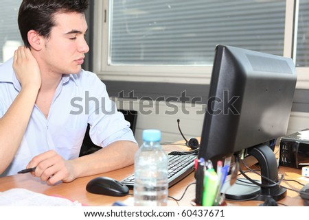Young man tense at work - stock photo