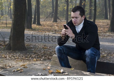 young man  the park and use a mobile phone - stock photo