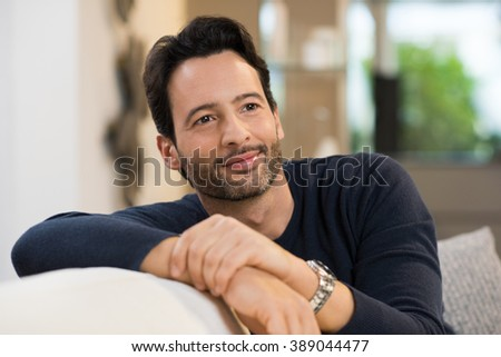 Young man thinking inspirations while sitting on couch in living room. Close up of a man in casual day dreaming about his future. Handsome latin guy thinking and looking away while resting at home.  - stock photo