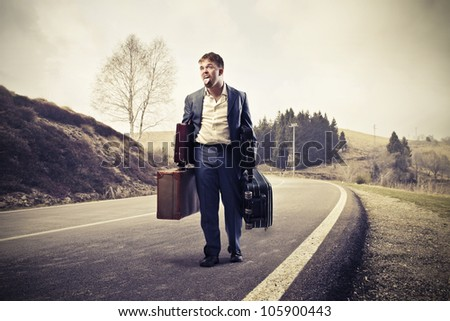 Young man tired of walking and carrying suitcases on a country road - stock photo