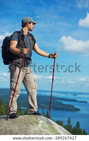 Young man tourist with backpack and sticks standing on mountain top and looking aside. - stock photo