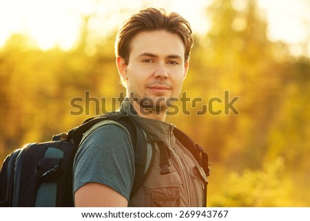 Young man tourist with backpack portrait. Red sunset light. - stock photo