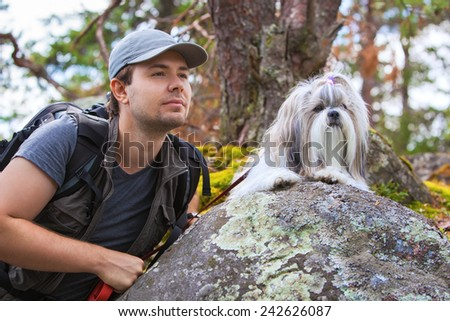 Young man tourist with shih-tzu dog portrait. - stock photo