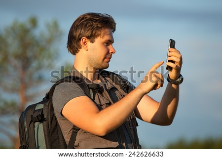 Young man tourist working with smartphone at travel outdoors. Searching route in navigator or making photos of location. - stock photo