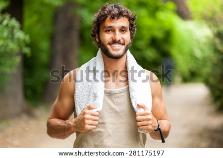Young man training himself outdoor and smiling at camera - stock photo