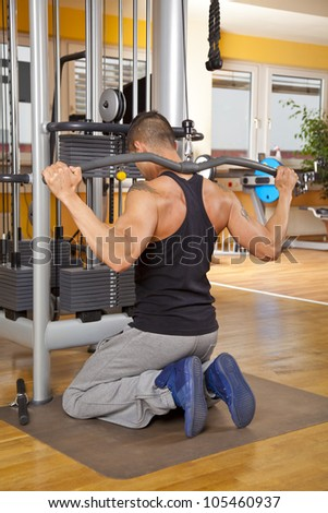 young man training latissimus in gym - stock photo