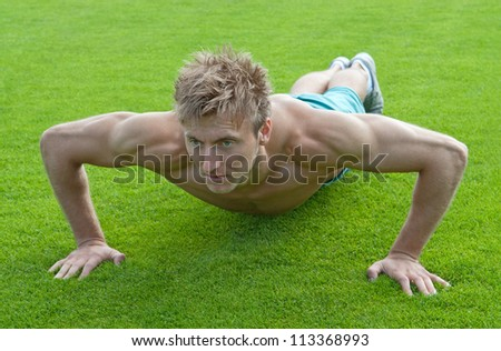 Young man training outdoors and doing push-ups on green grass. - stock photo
