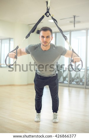 Young man training with suspension straps in modern gym facility. - stock photo