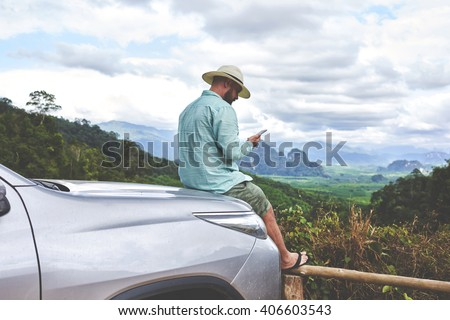 Young man traveler is watching video which he took on mobile phone during break between road trip in Asia. Hipster guy is reading text message on cell telephone, while is sitting on a suv hood - stock photo