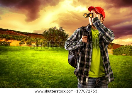 Young man traveler looking in binocular at the horizon standing on green valley. Portrait of male hiker with backpack wearing casual clothes.   - stock photo