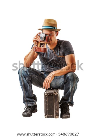 young man traveler takes a shot on vintage camera while sitting on a suitcase isolated on white background - stock photo