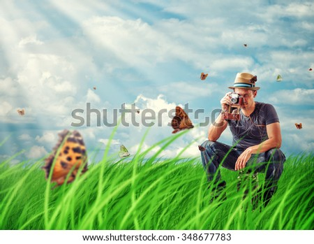 Young man traveller photographing butterflies on film retro camera in the Meadow - stock photo