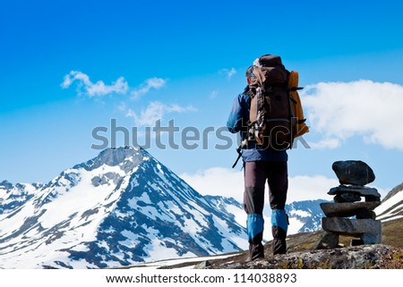 Young man trekking in the mountains - stock photo