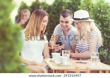 Young man trying to get a phone number from the girl in a cafe - stock photo
