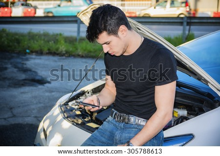 Young Man trying to repair a Car engine and seeking help from mobile phone - stock photo