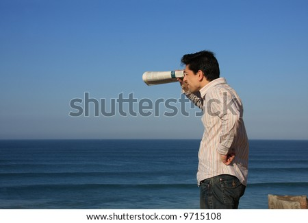 Young man trying to see something with a newspaper binocular - stock photo