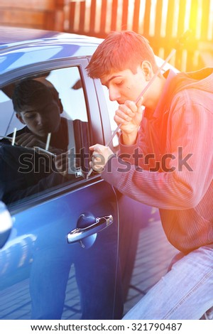 Young man trying to steal a car - stock photo
