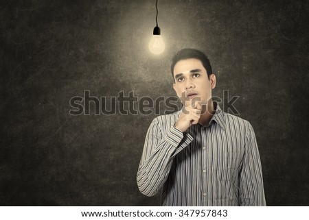 Young man under lit bulb thinking of idea in a classroom - stock photo