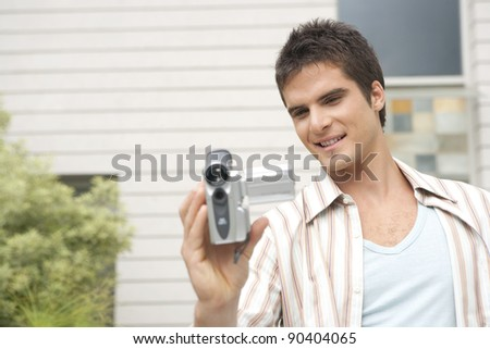 Young man using a digital video camera in home garden. - stock photo