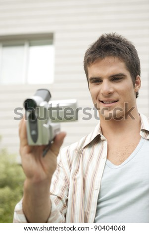 Young man using a digital video camera in office garden. - stock photo