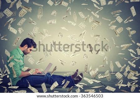 Young man using a laptop sitting on a floor building online business making money dollar bills cash falling down. Money rain. Beginner IT entrepreneur success economy concept - stock photo