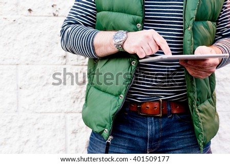 Young man using a tablet, Dressed casually. Jeans, Vest. Bright crisp post processed. Urban life style, technology, online, business, shopping, fashion and job hunting concept. - stock photo