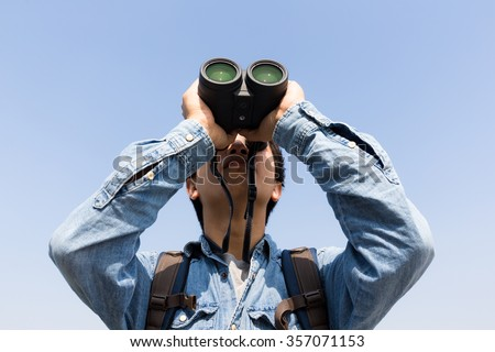 Young Man using binoculars with clear blue sky - stock photo