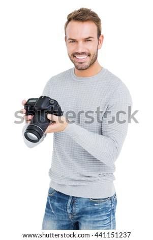 Young man using camera on white background - stock photo