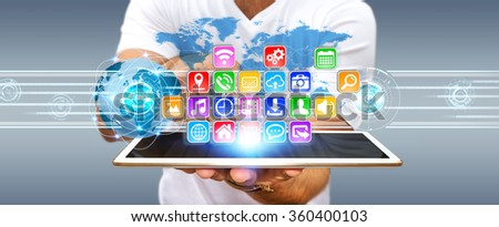 Young man using digital application with icons flying over his tablet - stock photo